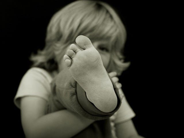 Toddler holding foot up to the camera