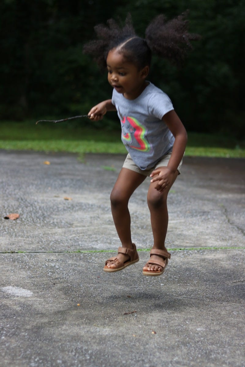 girl playing park jumping bobux driftwood sandal