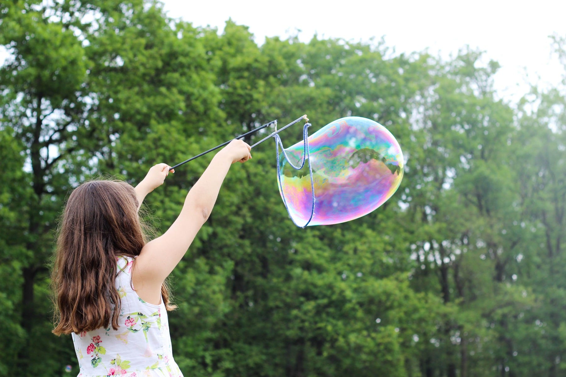 girl blowing bubbles outside