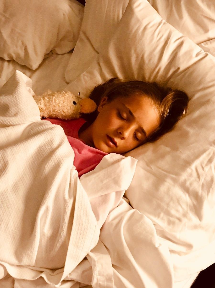 girl sleeping on bed with stuffed animal