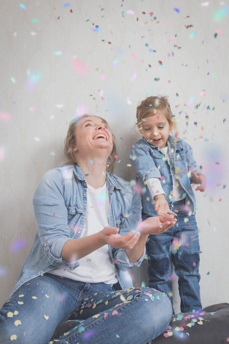 mom daughter playing with rainbow confetti in jean jackets