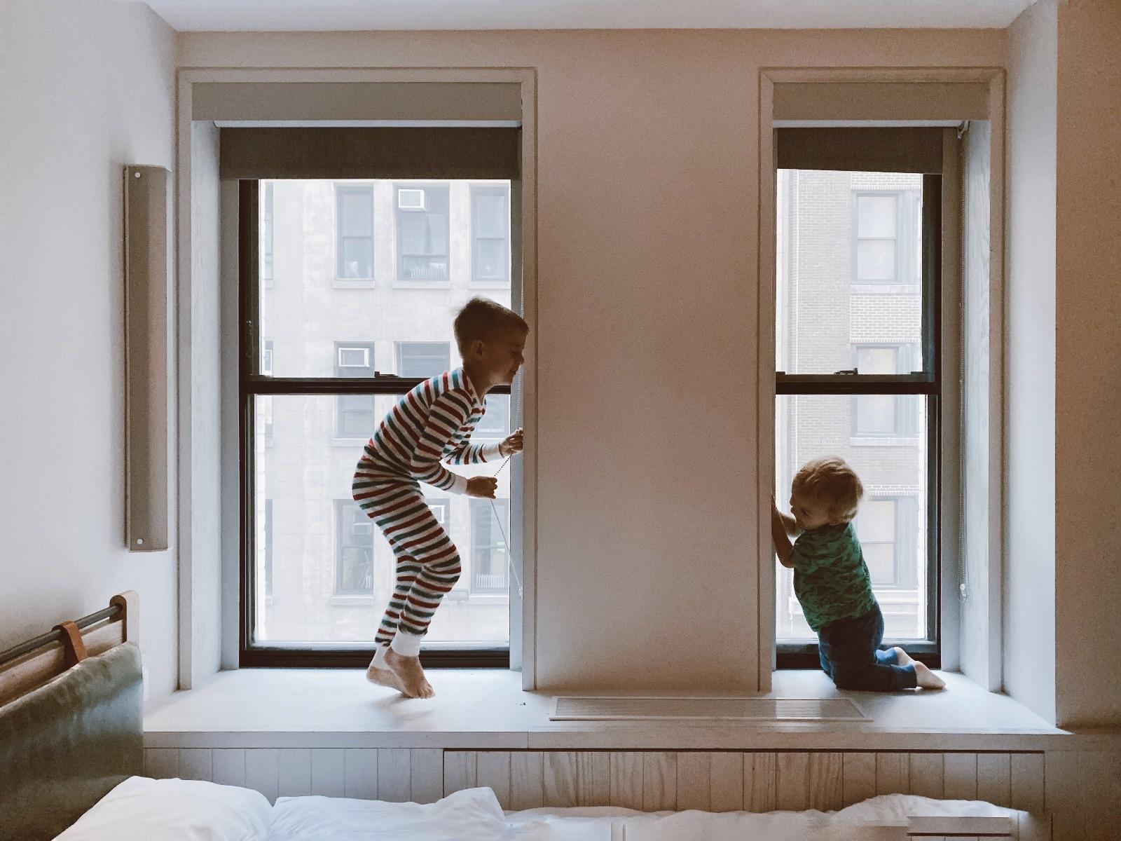 two kids playing beside glass windows in pajamas